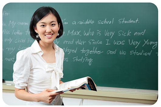 Female Asian teacher holds an open lesson plan book standing in front of a green chalkboard